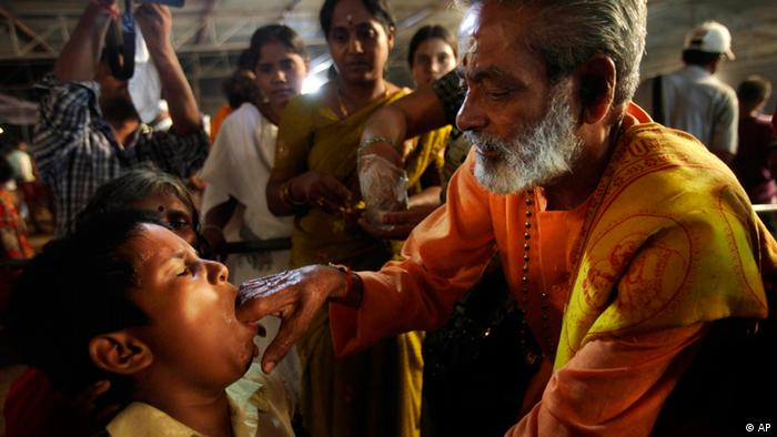 A member of the Goud family Harinath Goud administers live sardines smeared with secret herbs, believed to be a cure for asthma, to a patient in Hyderabad, India. (AP Photo/Mahesh Kumar A.)
