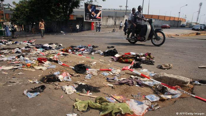 A man rides his motorbike past clothing and various items spread over the pavement at the scene of a stampede in Abidjan, on January 1, 2013. At least 60 people died and at least dozens were injured as crowds stampeded overnight during celebratory New Year's fireworks, Ivory Coast rescue workers said on January 1, 2013. AFP PHOTO/HERVE SEVI (Photo credit should read HERVE SEVI/AFP/Getty Images)