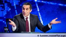 Bassem Raafat Muhammad Youssef (born March 22, 1974, Arabic: باسم رأفت محمد يوسف) is an Egyptian doctor, satirist, and the host of Al Bernameg (The Program), a satirical Egyptian news program broadcasted by CBC. The press has compared Youssef with American comedian Jon Stewart, whose satire program The Daily Show inspired Youssef to begin his career. Quelle: http://en.wikipedia.org/wiki/File:Bassem_Youssef_on_the_second_season_of_Al_Bernameg.jpg ***This work has been released into the public domain by its author, bassem youssef fan page. This applies worldwide.***