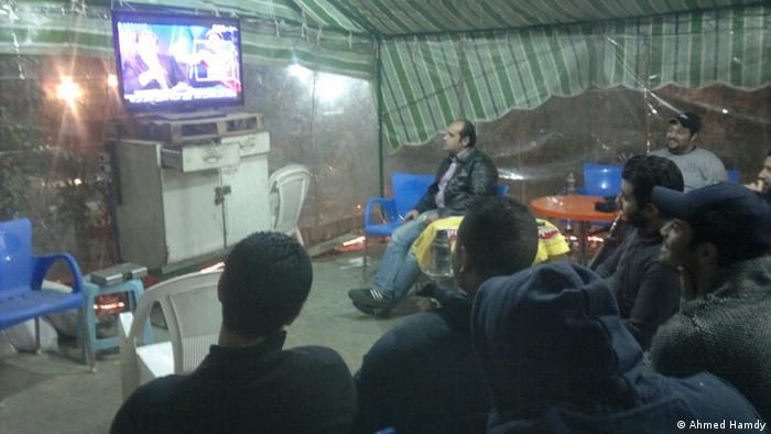 Bassem Youssef's program The Program: a sarcastic look at the Egyptian political conflicts. Photo title: People gathering in front of the television watching the program. Place: A cafe in Nasr City Copyright: Ahmed Hamdy