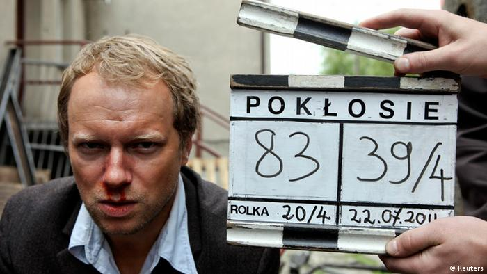 Polish actor Maciej Stuhr looks into a camera on set of the movie Poklosie (Aftermath) near Warsaw July 22, 2011. A film about a Polish village whose residents help massacre their Jewish neighbours in World War Two has forced Poles to confront one of the most troubling episodes of their past. Picture taken on July 22, 2011. REUTERS/Apple Film Production/Marcin Makowski (POLAND - Tags: ENTERTAINMENT) FOR EDITORIAL USE ONLY. NOT FOR SALE FOR MARKETING OR ADVERTISING CAMPAIGNS. THIS IMAGE HAS BEEN SUPPLIED BY A THIRD PARTY. IT IS DISTRIBUTED, EXACTLY AS RECEIVED BY REUTERS, AS A SERVICE TO CLIENTS