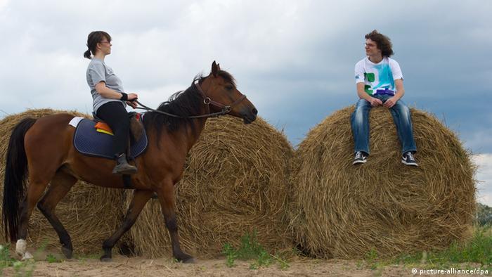 Eine junge Frau sitzt auf einem Pferd, ein junger Mann auf einem Strohballen.