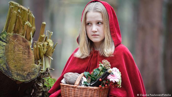 Ein Mädchen, verkleidet als Rotkäppchen, mit Korb im Wald.