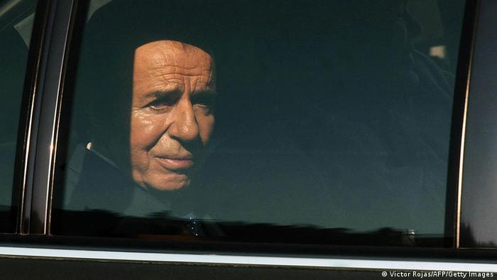 (FILES) Argentina's former President (1989-1999) Carlos Menem leaves a TV studio after the taping of an interview in Santiago, Chile, 09 September 2004. Argentine public prosecutor Alberto Nisman issued on May 22, 2008 in Buenos Aires, an arrest warrant for Carlos Menem for alleged covering up the trial investigating the attack to Jewish medical care fund AMIA in 1994, which left 85 people dead. The public prosecutor?s office also demanded Menem's withdrawal of parliamentary privileges --he is now senator for the province of La Rioja-- in case of a possible arrest. Menem is already going on trial next July 8 for allegedly smuggling weapons to Ecuador and Croatia from 1991 to 1995, a charge that can send him to prison for 12 years. AFP PHOTO / Victor ROJAS (Photo credit should read VICTOR ROJAS/AFP/Getty Images)