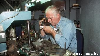 A diamond cutter in Antwerp examines a gemstone