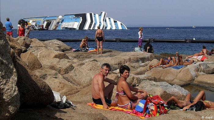 sunbathers sit in front of the wreck of Costa Concordia outside the port of Isola del Giglio (photo: AP Photo, Giacomo Aprili)