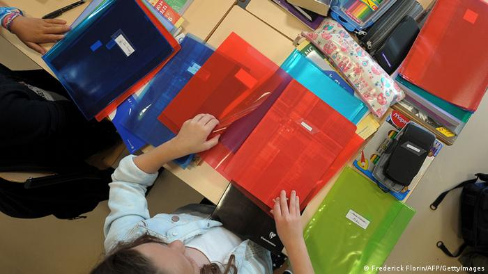 Pupils look on school supplies in a classroom