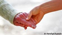 Senior and young holding hands over shiny white background. Chariclo - Fotolia 37184056