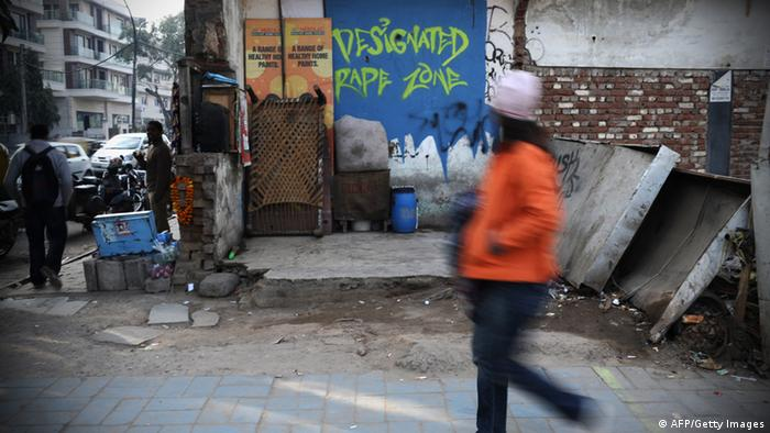 An Indian pedestrian walks past a graffiti sign which reads Designated Rape Zone (FINDLAY KEMBER/AFP/Getty Images)
