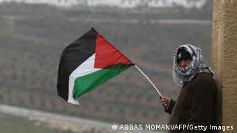 A Palestinian man waves his national flag on the sidelines of a march organized by inhabitants of the West Bank village Nabi Saleh on December 21, 2012, to protest against the expansion of Jewish settlements on Palestinian land. AFP PHOTO/ABBAS MOMANI (Photo credit should read ABBAS MOMANI/AFP/Getty Images)