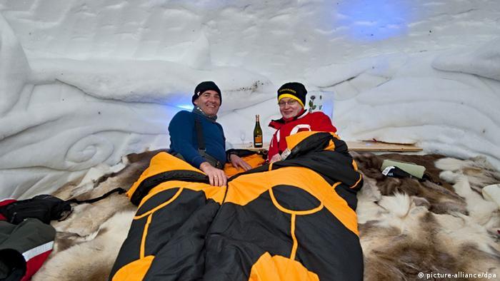 Zwei Menschen in Schlafsäcken in einem Iglu.