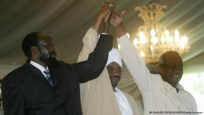KHARTOUM, SUDAN: Leader of the Sudan People's Liberation Movement (SPLM), Salva Kiir (L), holds hands with Sudanese President Omar al-Bashir (C) and second Vice President Ali Osman Taha at a low-key ceremony in Khartoum 11 August 2005, during which Kiir was sworn in as Sudan's first vice president after the death of his predecessor John Garang. Kiir, 54, pledged to follow his legacy and work for peace and unity in the war-ravaged country. He took office less than two weeks after Garang was killed in a helicopter crash that raised fears for the future of a peace deal that ended 21 years of war between southern rebels and the government in Khartoum. EDS NOTE: Removing extraneous sentence. AFP PHOTO/KHALED DESOUKI (Photo credit should read KHALED DESOUKI/AFP/Getty Images)