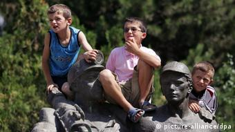 Three Albanian kids sit on the top of a communist era statue to whatch the convoy carrying Former Albanian President Sali Berisha(not in picture) in Tirana, Albania, on Tuesday 12 July 2005. Albania risked another election fiasco with Socialist Prime Minister Fatos Nano refusing to concede what the country's election commission said was a clear victory for rival Sali Berisha. Last week's vote was seen as an opportunity for formerly communist Albania to prove it now has the political maturity needed to join the European Union and NATO. EPA/ARMANDO BABANI +++(c) dpa - Report+++