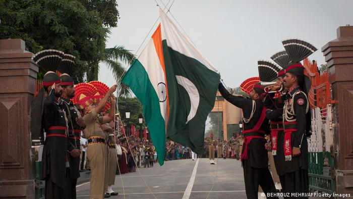 Pakistani and Indian soldiers lower the flags of their countries during a daily ceremony at the Wagha border near Lahore on July 17, 2011. The Wagha border is the only road border crossing between India and Pakistan. Every day a retreat ceremony takes place called 'the lowering of the flags' which has been held since 1959. The event is open to spectators who are able to view the spectacle from one side of either country's border. During the 45 minute ceremony Indian and Pakistani guards high-kick and stamp in a choreographed routine which ends in the lowering of both flags and the closing of the border gates. AFP PHOTO/BEHROUZ MEHRI (Photo credit should read BEHROUZ MEHRI/AFP/Getty Images)