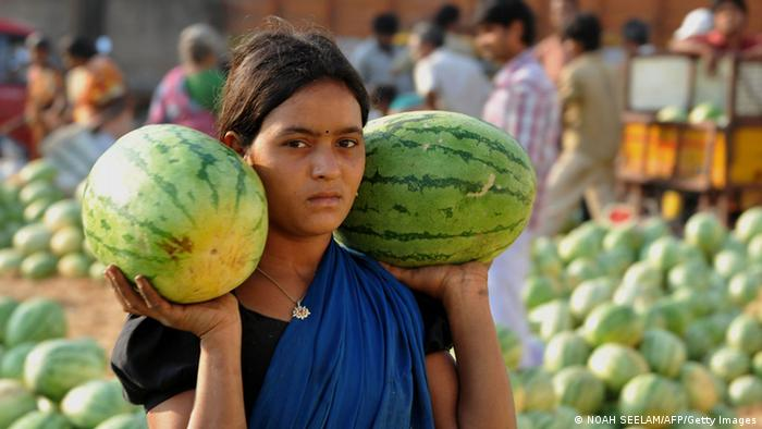 A female labourer carried away watermelons following an auction at the Gaddiannaram wholesale fruit market on the outskirts of Hyderabad on March 17, 2011. (Photo: NOAH SEELAM/AFP/Getty Images)