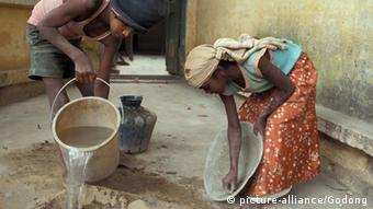 Two young women clean and do chores outside of a home (c) picture-alliance/Godang