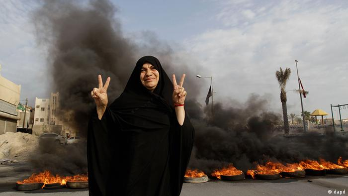 A Bahraini anti-government protester poses for a photograph flashing the victory sign in front of burning tires on a road in the village of Dumistan (Foto: Hasan Jamali/AP/dapd)