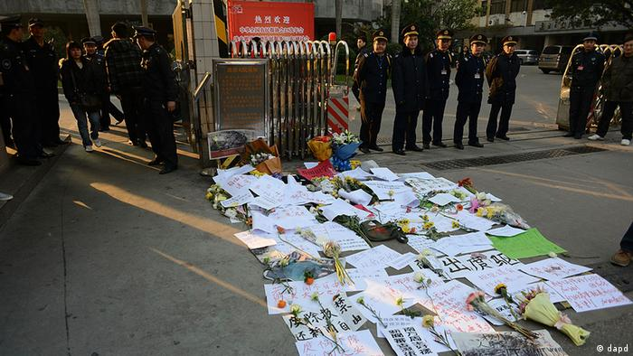 Security guards stand near protest banners and flowers are laid outside the headquarters of Southern Weekly newspaper in Guangzhou, Guangdong province Monday, Jan. 7, 2013. A dispute over censorship at the Chinese newspaper known for edgy reporting evolved Monday into a political challenge for China's new leadership as prominent scholars demanded a censor's dismissal and hundreds of protesters called for democratic reforms. (Foto:AP/dapd)