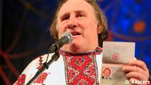 French film star Gerard Depardieu, wearing a local costume, shows his passport during a ceremony in the town of Saransk in the Mordoviya Republic, southeast of Moscow, January 6, 2013. Depardieu received a hug from Russia's President Vladimir Putin and a new Russian passport on Sunday after abandoning his homeland to avoid a new tax rate for millionaires. REUTERS/Yulia Chestnova (RUSSIA - Tags: ENTERTAINMENT POLITICS TPX IMAGES OF THE DAY)
