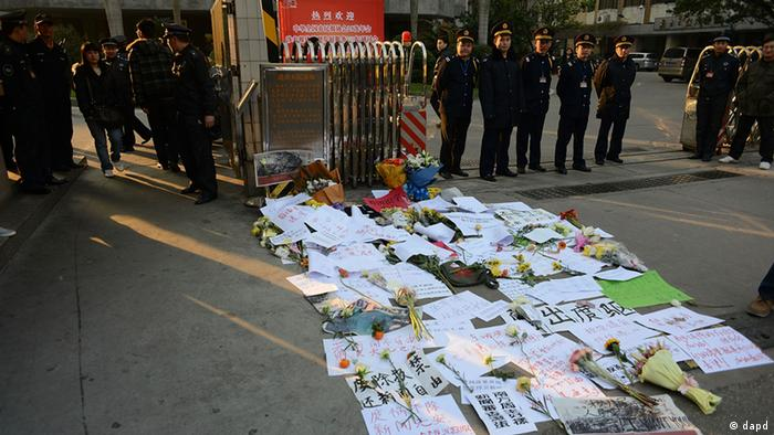 Security guards stand near protest banners and flowers are laid outside the headquarters of Southern Weekly newspaper in Guangzhou, Guangdong province Monday, Jan. 7, 2013. (Photo: AP / dapd)