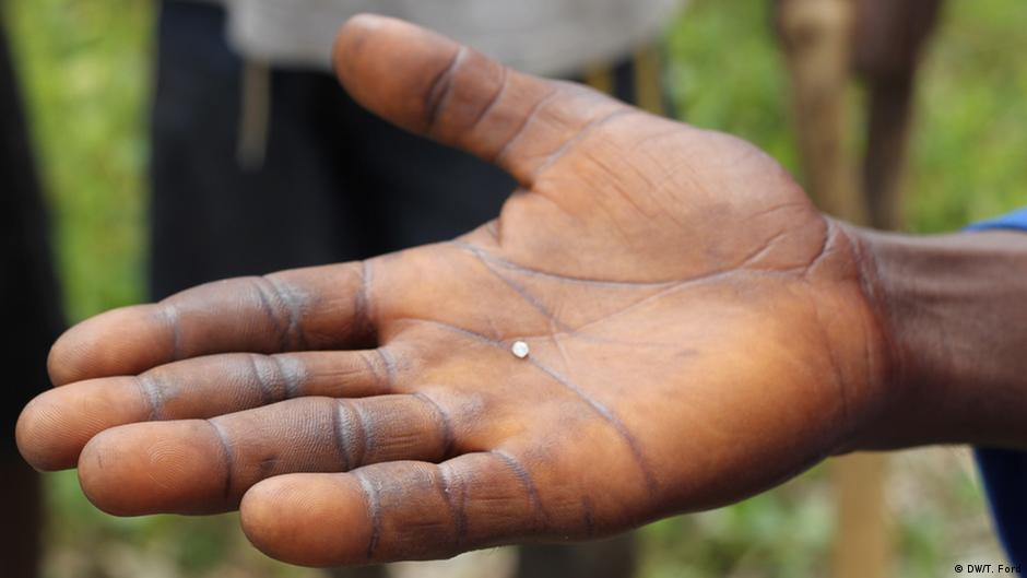 A man holding the diamond he discovered