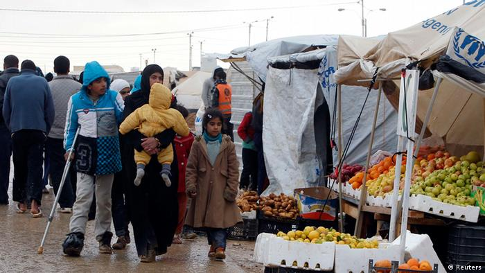 Syrians refugees walk near street vendors after heavy rain, at the Al-Zaatari refugee camp in the Jordanian city of Mafraq, near the border with Syria, January 8, 2013. REUTERS/Ali Jarekji (JORDAN - Tags: POLITICS CIVIL UNREST)