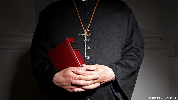 Church, a priest in a church, holding a bible. The holy cross on a chain around his neck, his hands folded. This image was produced to illustrate the items about sexual abuse in the church, religious boarding schools and summer camps. ANP XTRA ROOS KOOLE