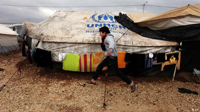 A Syrian refugee boy runs to his family tent at Zaatari Syrian refugee camp, near the Syrian border in Mafraq, Jordan, Tuesday, Jan. 8, 2013. Photo: Mohammad Hannon/AP/dapd)