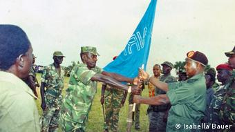 Soldiers symbolically exchange a flag as others watch