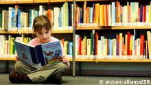 Die 8-jährige Lea sitzt in der Kinderbibliothek in Frankfurt (Oder) auf dem Fußboden und schaut sich das Buch Morgen früh um sechs kommt die kleine Hex' an, aufgenommen am 07.02.2008. Foto: Patrick Pleul dpa +++(c) dpa - Report+++