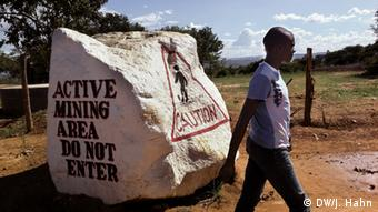 Photos shows a man walking past a large rock painted with words:Active mining area. Do not enter