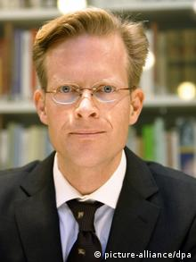 A man with sandy-blonde hair and round glasses starse intently at the camera without really smiling. (Photo: (c) dpa - Bildfunk)