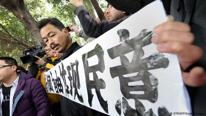 A protester calling for greater media freedom outside the headquarters of Nanfang Media Group in Guangzhou holds up a banner saying freedom of press reflects the public's opinion in Chinese on January 9, 2013. A Chinese weekly newspaper at the centre of rare public protests about government censorship will publish as usual on January 10, a senior reporter said, following reports of a deal to end the row. The row at the popular liberal paper, which had an article urging greater rights protection replaced with one praising the ruling communist party, has seen demonstrators mass outside its headquarters in the southern city of Guangzhou. AFP PHOTO (Photo credit should read STR/AFP/Getty Images)