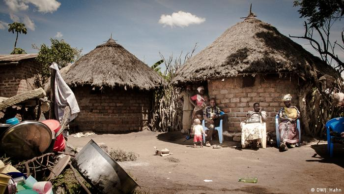 People outside their huts in the region of Tanzania's Mara gold mine