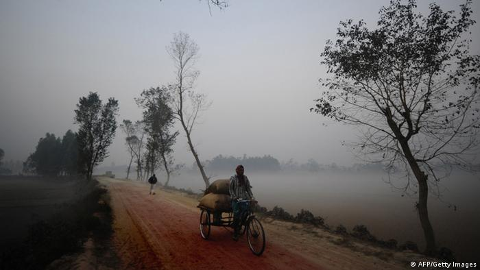 A rickshaw-bicycle driver rides in Dinajpur some 430km north form Bangladeshi capital Dhaka on December 22, 2010. The spell of cold weather that gripped the country, causes hardship for many of the population who aren't equipped to cope with colder temperatures. AFP PHOTO/Munir uz ZAMAN (Photo credit should read MUNIR UZ ZAMAN/AFP/Getty Images)