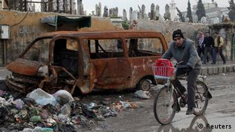 A man rides his bicycle in Aleppo city January 9, 2013. REUTERS/Muzaffar Salman (SYRIA - Tags: CONFLICT)