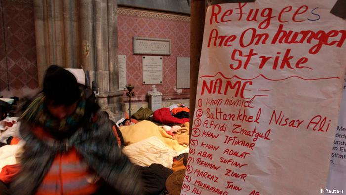 A white flip-chart with red handwriting stands in the foreground of a scene inside a church with refugees lying or sleeping on the ground. (Photo: REUTERS/Herwig Prammer)