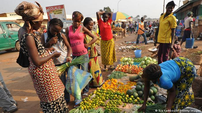 Women buy vegetables in a market (photo: SIA KAMBOU/AFP/Getty Images)