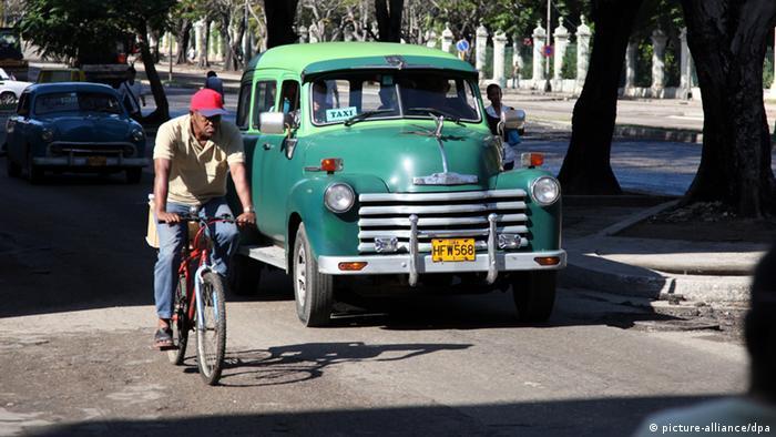 Ein Taxi überholt im kubanischen Havanna einen Radfahrer auf einer Straße (Foto: Friso Gentsch/dpa)