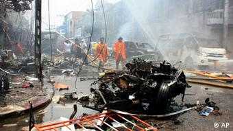 Thai fire fighters walk near a wreckage of a car while others trying to put off fire at a building after the car bomb blasted in Yala, southern Thailand, Saturday, March 31, 2012. (Photo: AP)