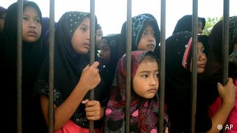 Thai-Muslim girls look from outside the gate as police officers investigate at Guwing school building that was burnt down by suspected Muslim separatists in Mayor district of Pattani province, southern Thailand Thursday, Aug. 2, 2012. (Photo:Sumeth Panpetch/AP/dapd)