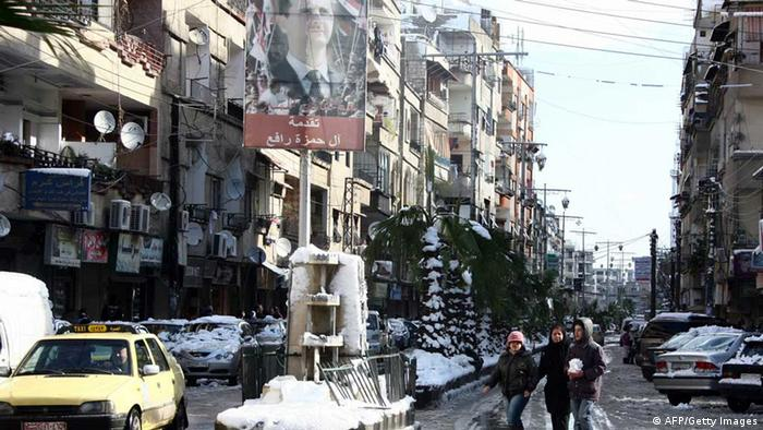 People walk past a poster featuring Syria's president in a street covered with snow on January 10, 2013 in the Syrian capital of Damascus. Snow carpeted Syria's war-torn cities but sparked no let-up in the fighting, instead heaping fresh misery on a civilian population already enduring a chronic shortage of heating fuel and daily power cuts. AFP PHOTO / LOUAI BESHARA (Photo credit should read LOUAI BESHARA/AFP/Getty Images)