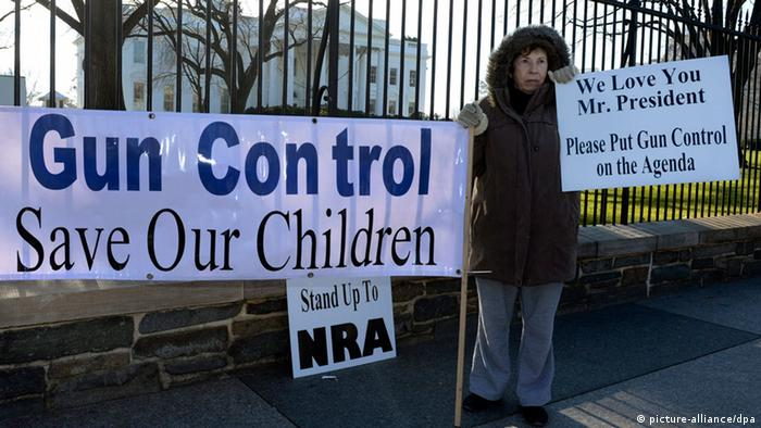 A supporter of gun control stands with signs that read; 'Gun Control Save Our Children' (L), 'We Love You Mr. President, Please Put Gun Control on the Agenda' (R) and 'Stand Up To NRA' (back), outside the White House in Washington DC, USA, 15 December 2012. Reports state on 14 December 2012 that a gun man unleashed a hail of gunfire that killed 20 children and six adults at a school in Newtown, a quiet, affluent suburb of 27,500 people about 100 kilometres north-east of New York City. He then killed himself inside Sandy Hook Elementary School, having previously killed his mother. EPA/MICHAEL REYNOLDS