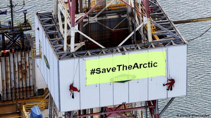 Protestors unfurl a green sign atop an oil rig (Photo: EPA/NIGEL MARPLE (c) dpa)