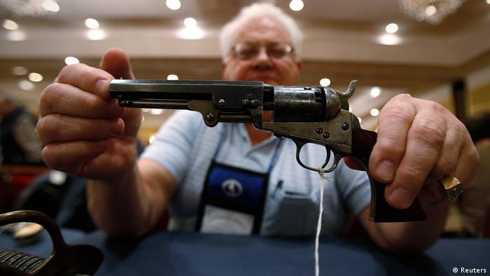 Jedan Amerikanac ponosno pokazuje primjerak iz svoje kolekcije starog oružja