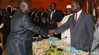 Central African Republic President Francois Bozize, right, shakes hands with Michel Djotodia, leader of the Seleka rebel alliance, as heads of state and other participants applaud, during peace talks in Libreville, Gabon, Friday, Jan. 11, 2013. Officials say that the rebel group controlling much of the northern half of the country have agreed to enter into a coalition with the government. The deal will allow President Francois Bozize to stay in office until his current term expires in 2016. (Foto:Joel Bouopda Tatou/AP/dapd)