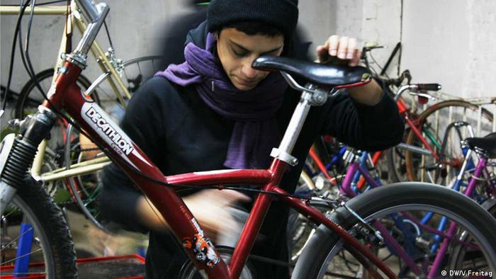 Rebeca Paz works on a bicycle at La Tabacalera in Madrid