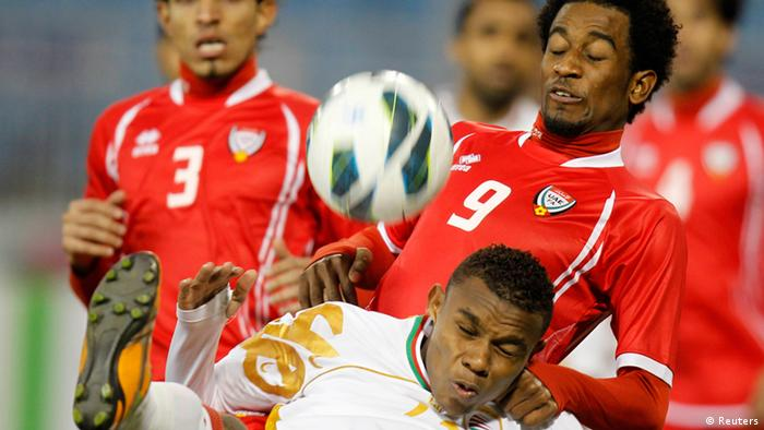 UAE's Abdelaziz Hussain (top) fights for the ball with Oman's Juma Darwish Al-Maashari during their Gulf Cup Tournament soccer match at Khalifa Sports City in Isa Town January 11, 2013. REUTERS/Mohammed Dabbous (BAHRAIN - Tags: SPORT SOCCER)