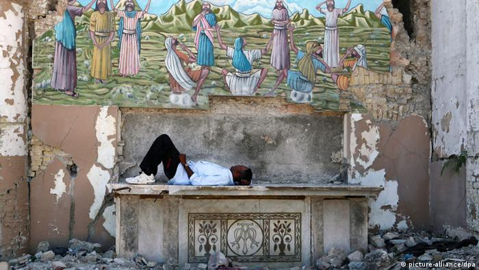 epa03530324 A man rests on the altar of a destroyed church in Port-Au-Prince, Haiti, 10 January 2013. Haiti commemorates the third anniversary of the magnitude-7 earthquake that left more than 300,000 dead when it struck on 12 January 2013. EPA/ORLANDO BARRIA +++(c) dpa - Bildfunk+++