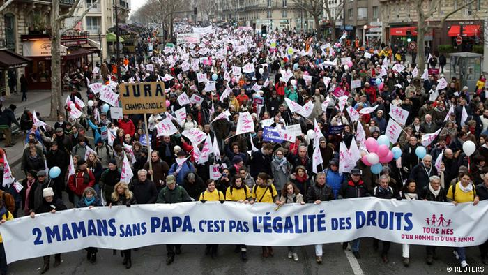 A large group of demonstrators marches behind a banner, Photo: Philippe Wojazer